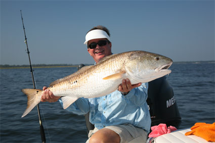 "SWEET REVENGE!  The author shows off a huge red drum after returning to North Carolina, where he accidentally severed his wrist during a ""blown out"" show a year earlier."